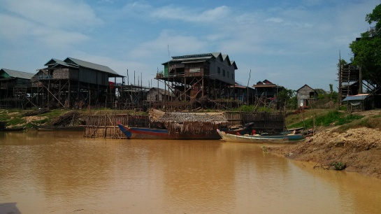 They build the houses up several stories because the entire town floods during the rainy season and they have to take boats/jetpacks to school